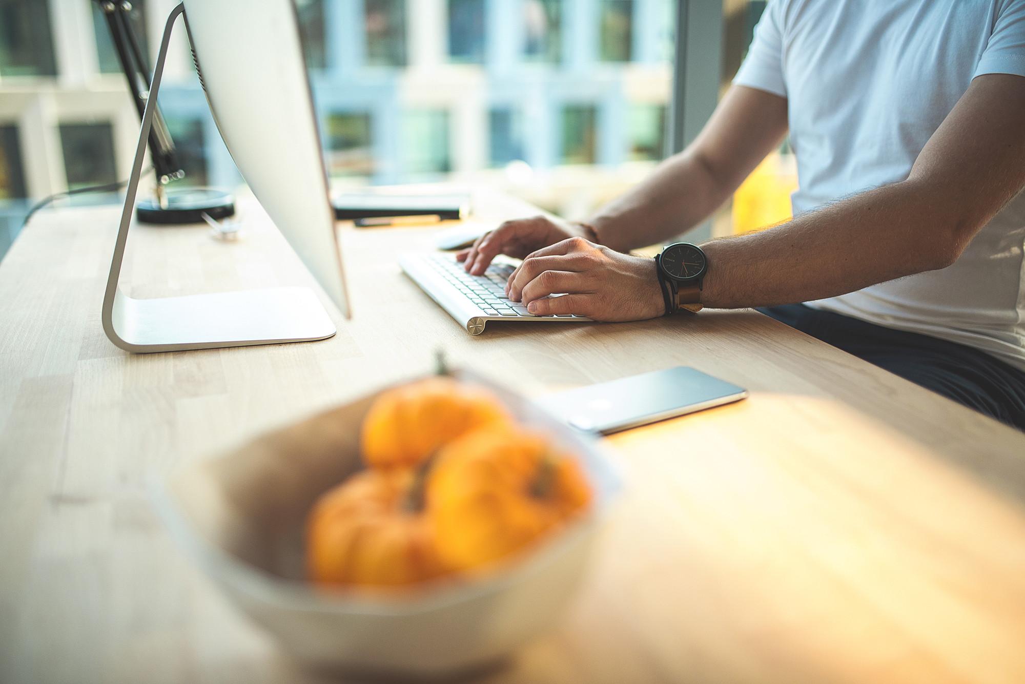 Mann schreibt auf einer Tastatur